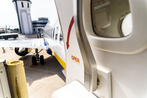 Open door of a plane parked while passengers disembark.