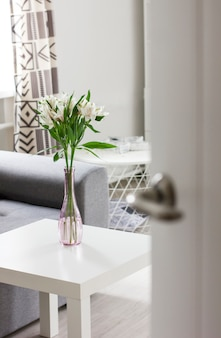 Open door to room with bouquet of flowers on table, scandinavian interior