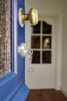 キーと家の形をしたキーホルダーで新しい家への扉を開きます。住宅ローン、投資、不動産、不動産、新築住宅コンセプト事業