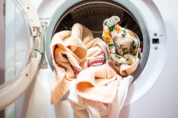 Open door of the washing machine with linen