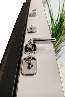 An open door with locks. modern door with chrome metal handles and locks. interior elements. home security. close-up of lock on armored door. place for your creativity with space for text or logo