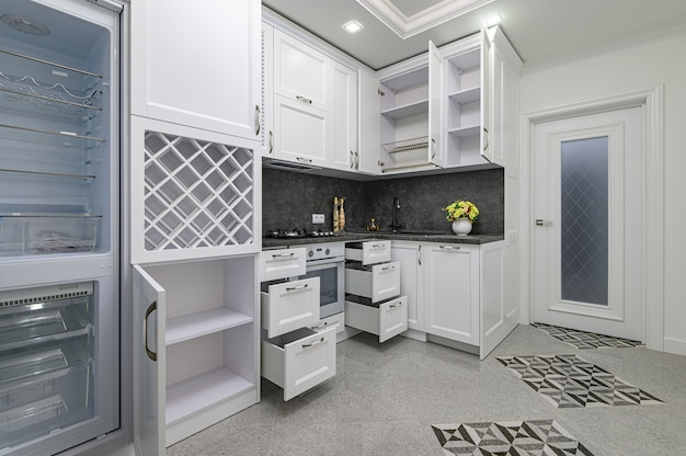 Открытые двери и ящики открываются на современной белой кухне