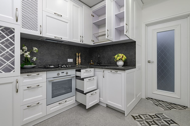 モダンな白いキッチンでドアと引き出しが開く