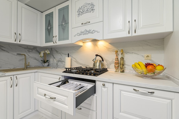 クラシックなスタイルのモダンな白い木製キッチンのカトラリー付きオープン引き出し