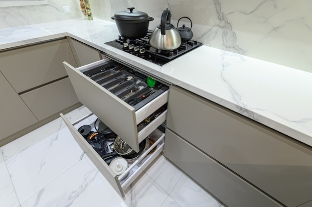 Open drawer with cutlery at modern white woden kitchen in classic style