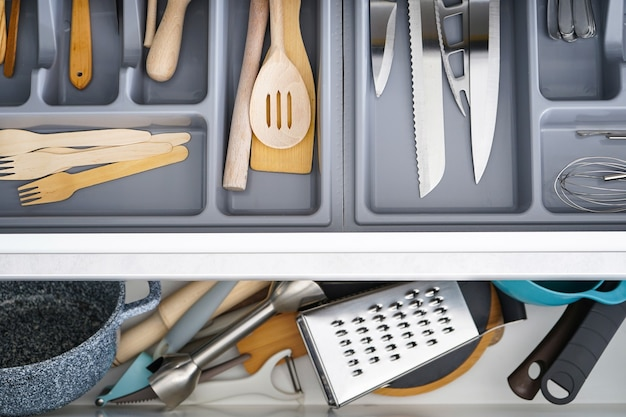 キッチンのさまざまな道具やカトラリーを備えたオープンドロワー、フラットレイ。