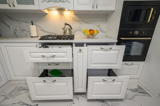 クラシックなスタイルのモダンな白い木製キッチンのキッチン用品付きのオープン引き出し