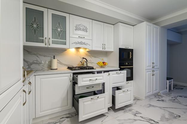Открытые ящики с посудой на современной кухне white woden в классическом стиле