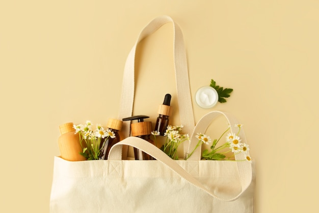 Open ecofriendly cotton reusable bag with the different containers fresh chamomile in it