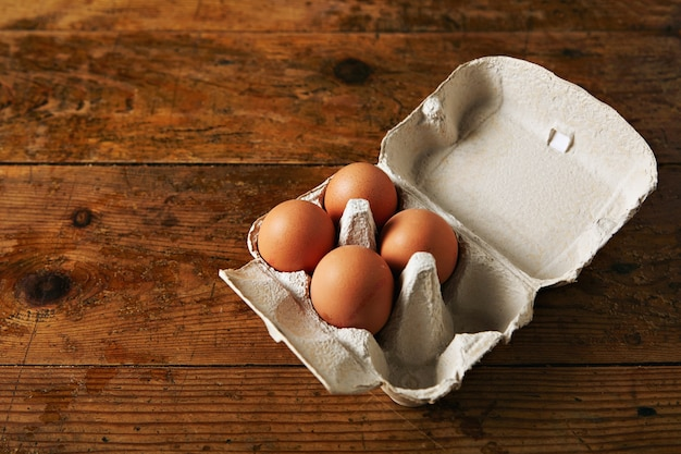 粗い素朴な茶色の木製テーブルに4つの茶色の卵を含む6つの卵の卵パックを開きます