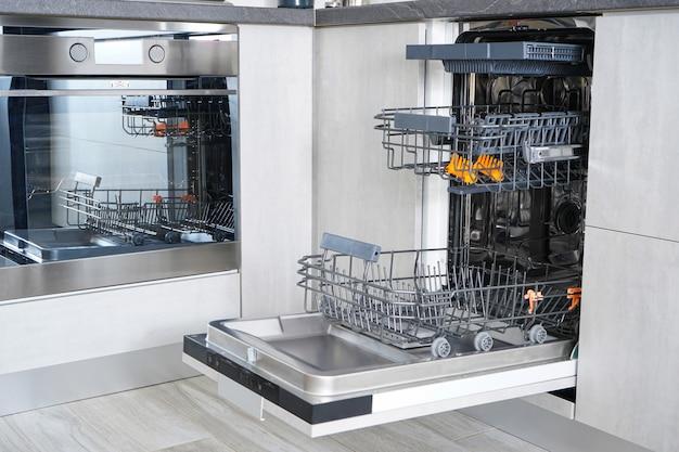 Открытая пустая автоматическая посудомоечная машина на кухне