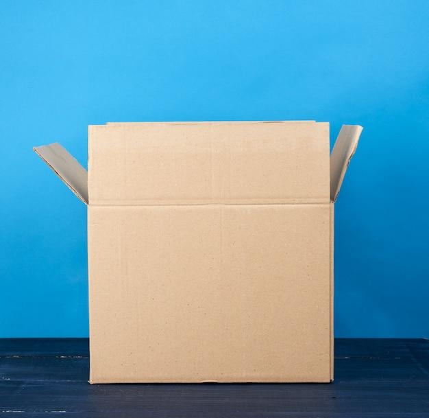 商品を輸送するための空の茶色の長方形の段ボール箱を開く