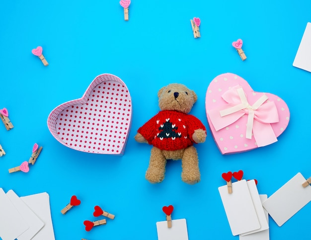 Open empty cardboard box in the form of a heart and little brown teddy bear on a light blue