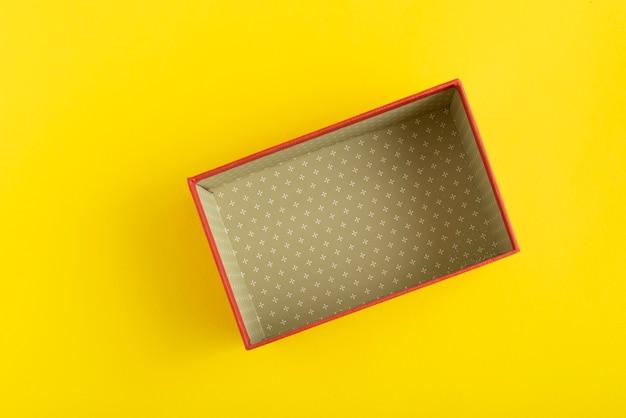 Откройте пустую картонную коробку на желтом фоне. вид сверху.