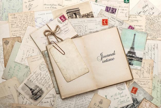 空の日記帳、古い手紙、フランスのポストカードを開きます。ノスタルジックなヴィンテージスクラップブックの背景とサンプルテキストjournalintime(diary)in french