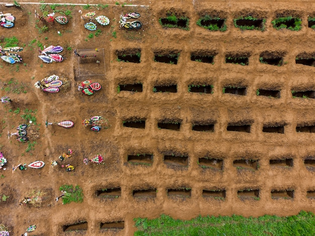Open empty graves among the green lawn, aerial drone view of emty tombs.