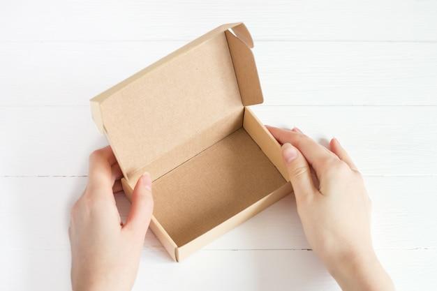 Open empty kraft box on white wooden background