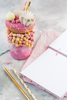Open empty note book near pink freak shake