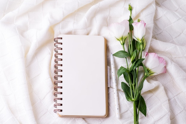 Open empty notebook and bouquet of flowers eustoma on blanket background. beautiful greeting card in vintage style. flat lay.