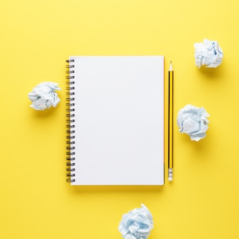 Open empty notebook, pencil and crumpled papers on yellow background. creation process or creative attempts.