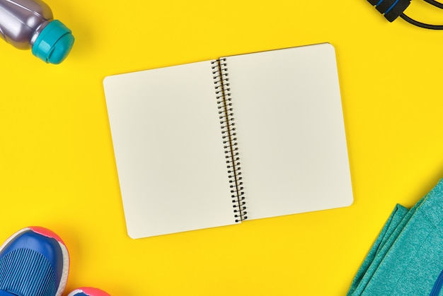 Open empty notebook and sports women's clothing for sports