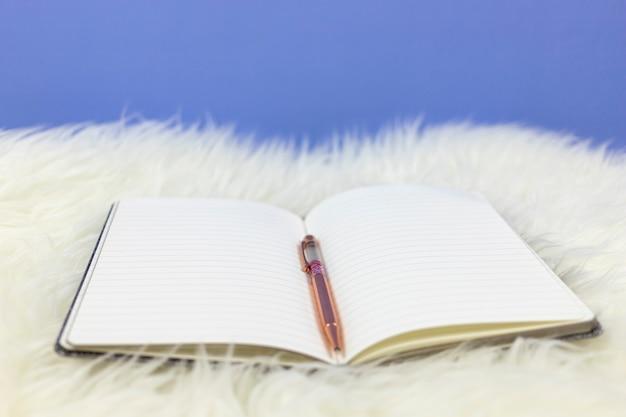 백색 모피 배경에 분홍색 펜으로 빈 노트북을 엽니 다.