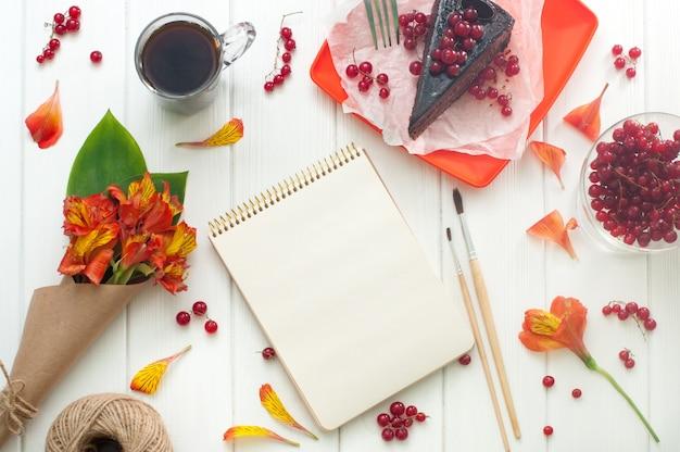 一杯のコーヒー、ケーキ、花と空のノートブックを開く
