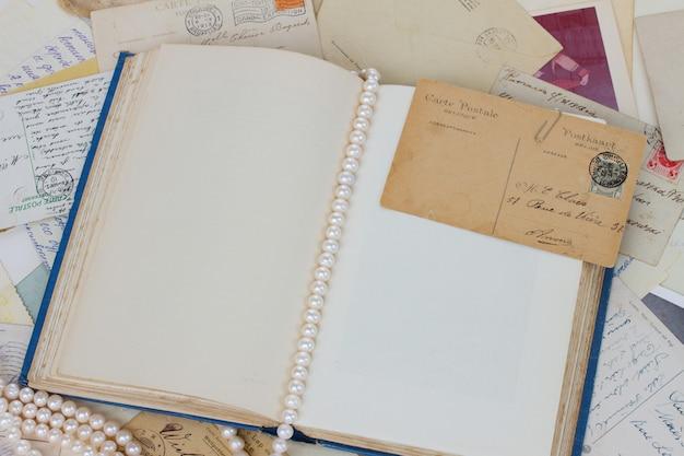 Откройте пустую старую книгу со старинными открытками и жемчугом старинный фон с копией пространства