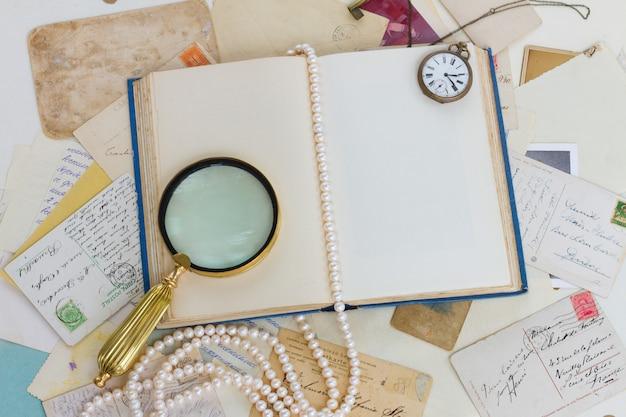 Открытая пустая старая книга с лупой, антикварными открытками и жемчугом старинный фон