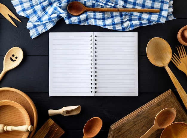 Open empty paper notebook with white sheets in a line on a spring in the middle of wooden kitchen items