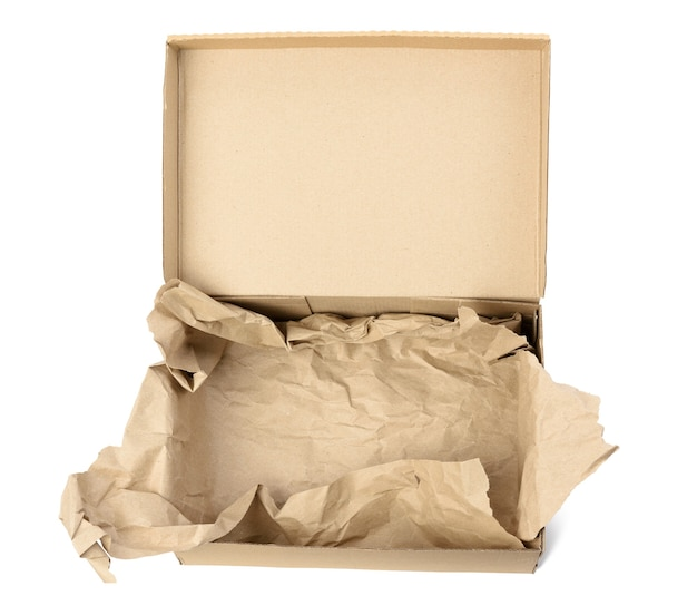 Open empty rectangular brown cardboard box for transportation and packaging of goods isolated on white background, top view. at the bottom is a piece of brown paper Premium Photo