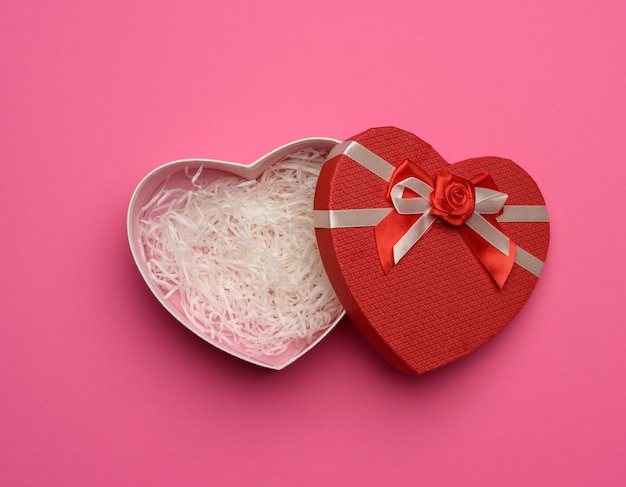 Open empty red cardboard box in the form of a heart on a pink background, top view