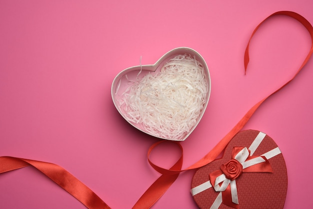 Open empty red cardboard box in the form of a heart on a pink