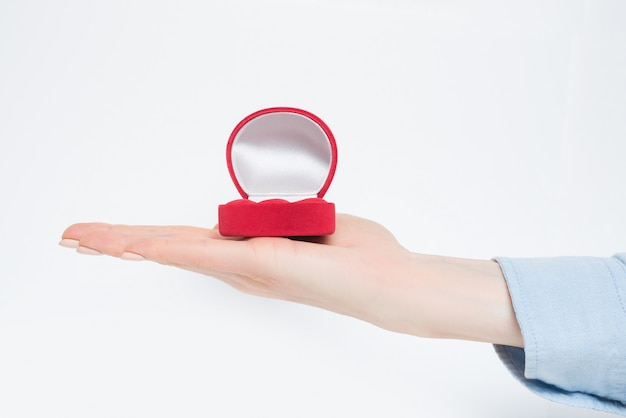 Open empty red jewelry box on female hand.