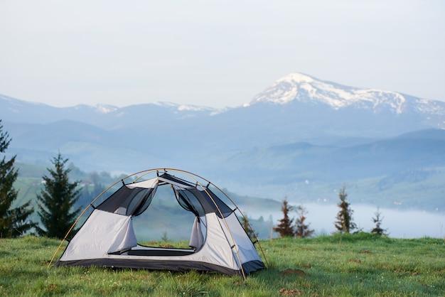Открытая пустая небольшая туристическая палатка на травянистом холме