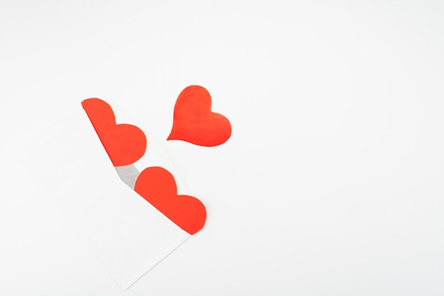 Open envelope and three red paper hearts on a white background with place for text
