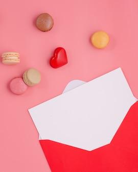 Открытый конверт с пустым бланком, сердцем и миндальным печеньем на розовом фоне