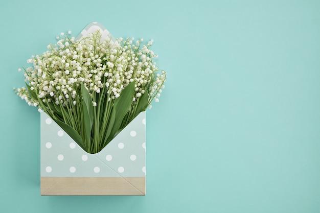 청록색 배경에 은방울꽃이 있는 열린 봉투
