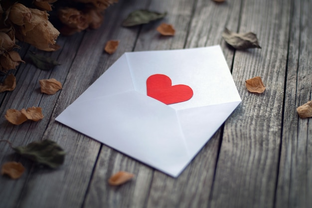 Open envelope with red paper heart among dry roses petals