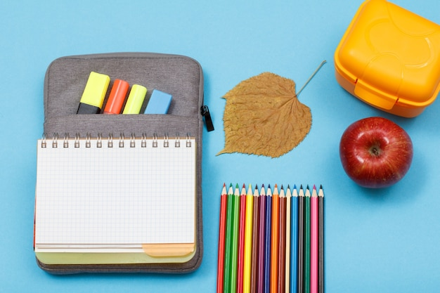 Открытая тетрадь на сумке-пенале с цветными фломастерами и маркером, ланч-бокс, яблоко, сухой лист и цветные карандаши на синем фоне. вид сверху. снова в школу концепции. школьные принадлежности