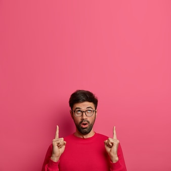 Open eyed bearded adult man points index fingers above