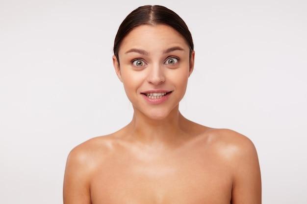 裸の肩でポーズをとっている間、驚くほど見ていると驚くほど眉を上げるカジュアルな髪型の目を開いた素敵な若いブルネットの女性