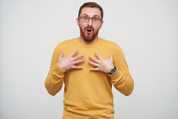 Ragazzo barbuto piuttosto giovane con gli occhi aperti in occhiali con i capelli corti castani che tiene i palmi sul petto e guarda sorpreso, isolato