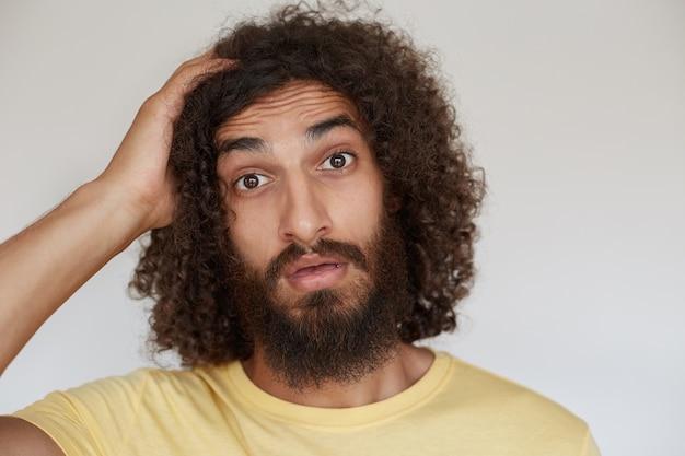 彼の頭に手のひらを保持し、開いた口で驚いて見ているひげを持つ開いた目のかなり若いブルネットの巻き毛の男、驚いて額にしわを寄せる