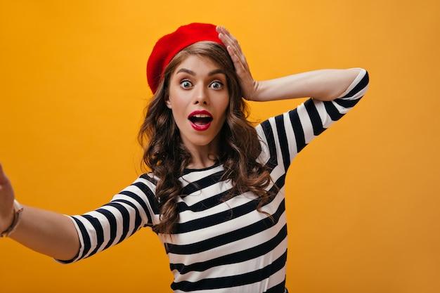 La donna dagli occhi aperti in berretto rosso fa selfie. ragazza riccia sorpresa con cappello luminoso in maglioni moderni a strisce che esamina la macchina fotografica.