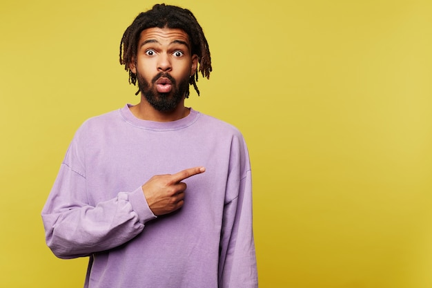 Open-eyed young attractive dark skinned brunette bearded male showing aside with forefinger and raising surprisedly eyebrows, standing against yellow background