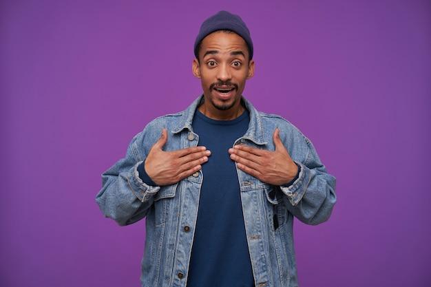Giovane maschio attraente dalla pelle scura dagli occhi aperti con la barba che tiene i palmi sul petto e guardando con la faccia sorpresa, in posa sopra il muro viola in abbigliamento casual