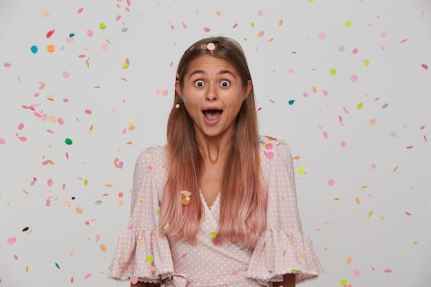 Молодая привлекательная женщина с открытыми глазами и длинными светло-каштановыми волосами с естественным макияжем стоит над белой стеной и разноцветным конфетти, удивленно глядя с открытым ртом