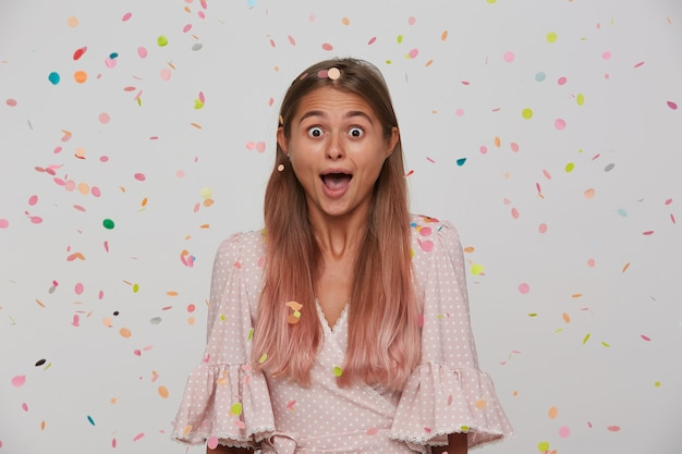Open-eyed young attractive woman with light brown long hair wearing natural makeup while standing over white wall and multicolored confetti, looking surprisedly  with opened mouth