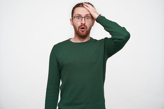 Giovane uomo con la barba e gli occhi aperti con i capelli corti castani che guarda con stupore e tiene il palmo della mano sulla fronte, indossa un maglione verde mentre posa